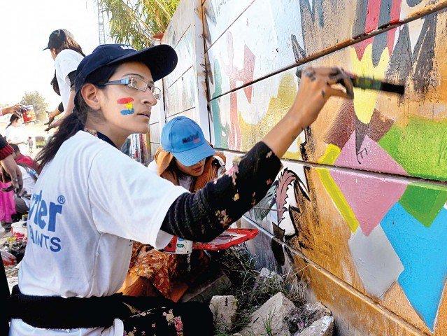 A student paints walls on Allama Iqbal Road, Mustafabad. PHOTO: EXPRESS/IJAZ MAHMOOD
